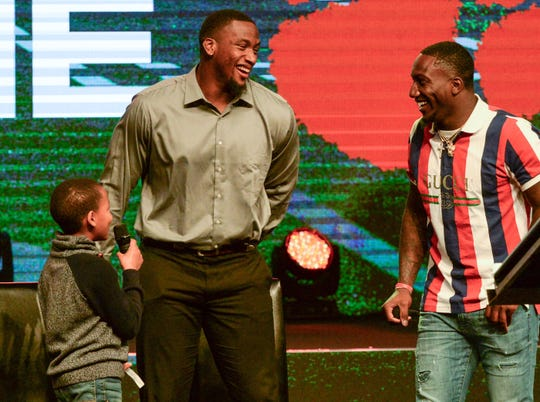 Former Clemson Tiger Clelin Ferrell, left, and Deebo Samuel, right, South Carolina Gamecock football player, listen to Ethan Adams of La France Elementary School ask a question about their future non-football careers during the Coaches 4 Character event at Relentless Church in Greenville Tuesday.