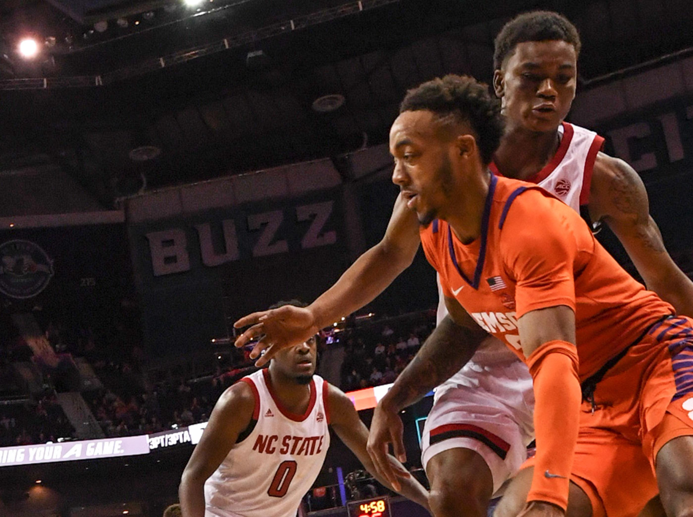 Clemson guard Marcquise Reed (2) dribbles around N.C. State guard C.J. Bryce(13) during the first half at the Spectrum Center in Charlotte, N.C. Tuesday, March 12, 2019.