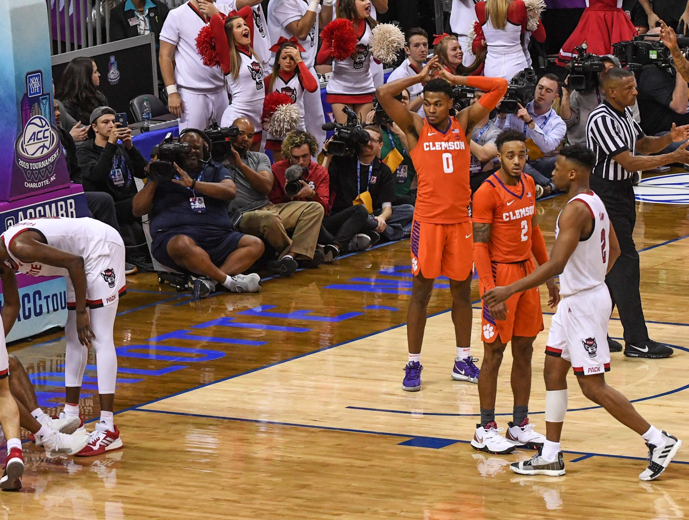Clemson center Clyde Trapp (0), right, reacts after he was called for fouling N.C. State guard Markell Johnson(11) with less than three seconds in the game during the second half at the Spectrum Center in Charlotte, N.C. Tuesday, March 12, 2019. Johnson made both free throws and N.C. State won 59-58.