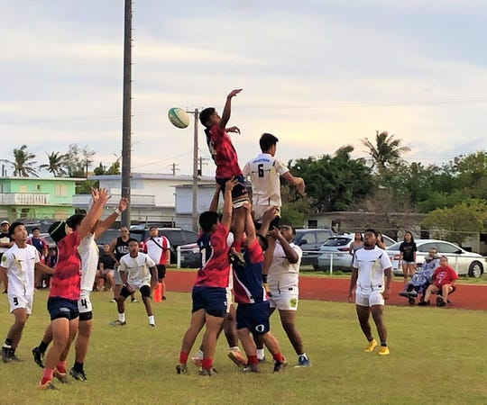 The John F. Kennedy Islanders, in white, battle the Okkodo Bulldogs for possession during IIAAG Boys Rugby Wednesday at GW field.