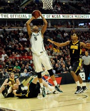 A rough-and-tumble 2013 Big Ten Tournament matchup between Michigan State and Iowa is depicted in this photo, as the Spartans' Adreian Payne (5) shoots against Iowa during a 59-56 win. Zach McCabe and Mike Gesell are on the ground; Melsahn Basabe is trailing.