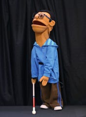 A puppet representing a visually-impaired  child is used by members of the Joseph Maley Friends Puppet Troupe putting on a puppet show for students at Our Lady of Lourdes School, as part of a Disabilities Awareness program, Monday, March 11, 2019.  The Joseph Maley Foundation uses differently-abled puppets to teach children about disabilities.