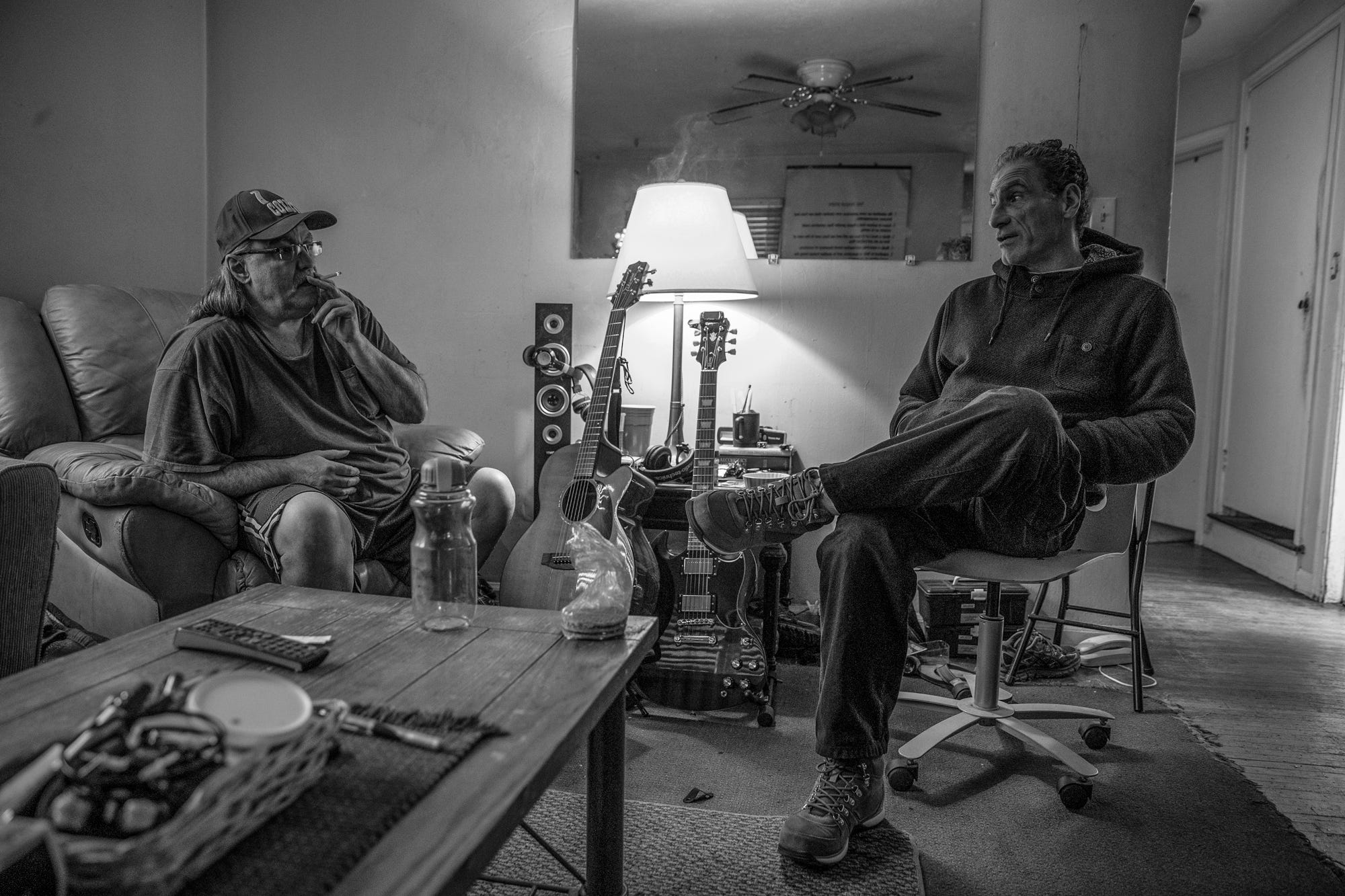 Ed Correll (left), a resident who lives in the halfway house in front of Pazzarelli's home, smokes a cigarette during an afternoon meeting in Indianapolis on Tuesday, Jan. 29, 2019.