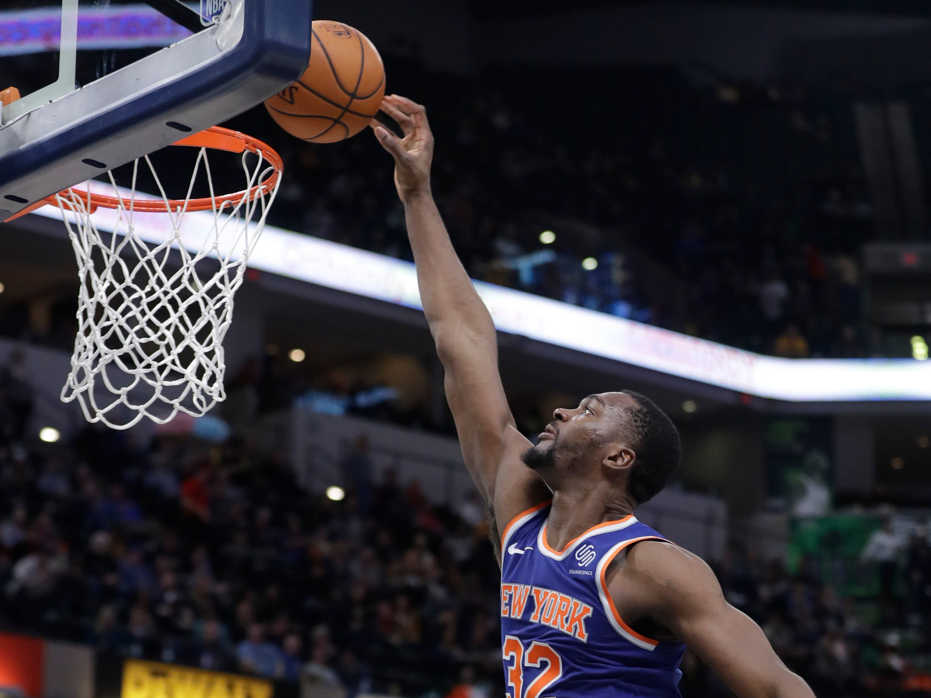 New York Knicks' Noah Vonleh (32) goes up for a dunk over Indiana Pacers' Thaddeus Young (21) during the first half of an NBA basketball game Tuesday, March 12, 2019, in Indianapolis.