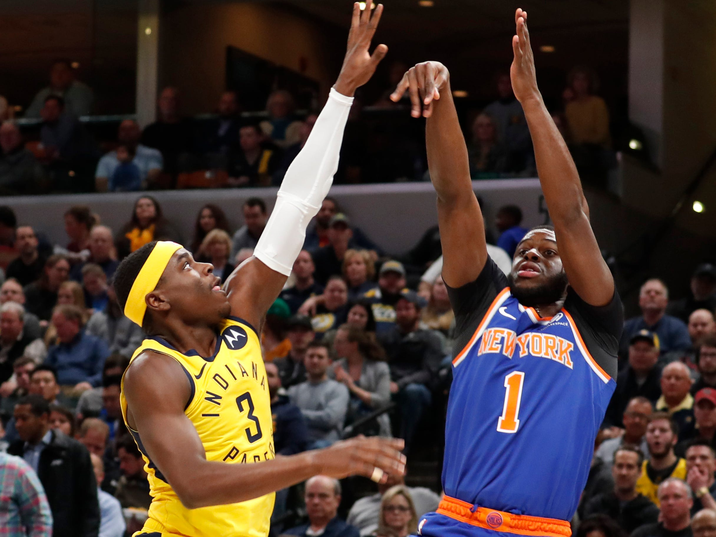 Mar 12, 2019; Indianapolis, IN, USA; New York Knicks guard Emmanuel Mudiay (1) takes a shot against Indiana Pacers guard Aaron Holiday (3) during the first quarter at Bankers Life Fieldhouse.