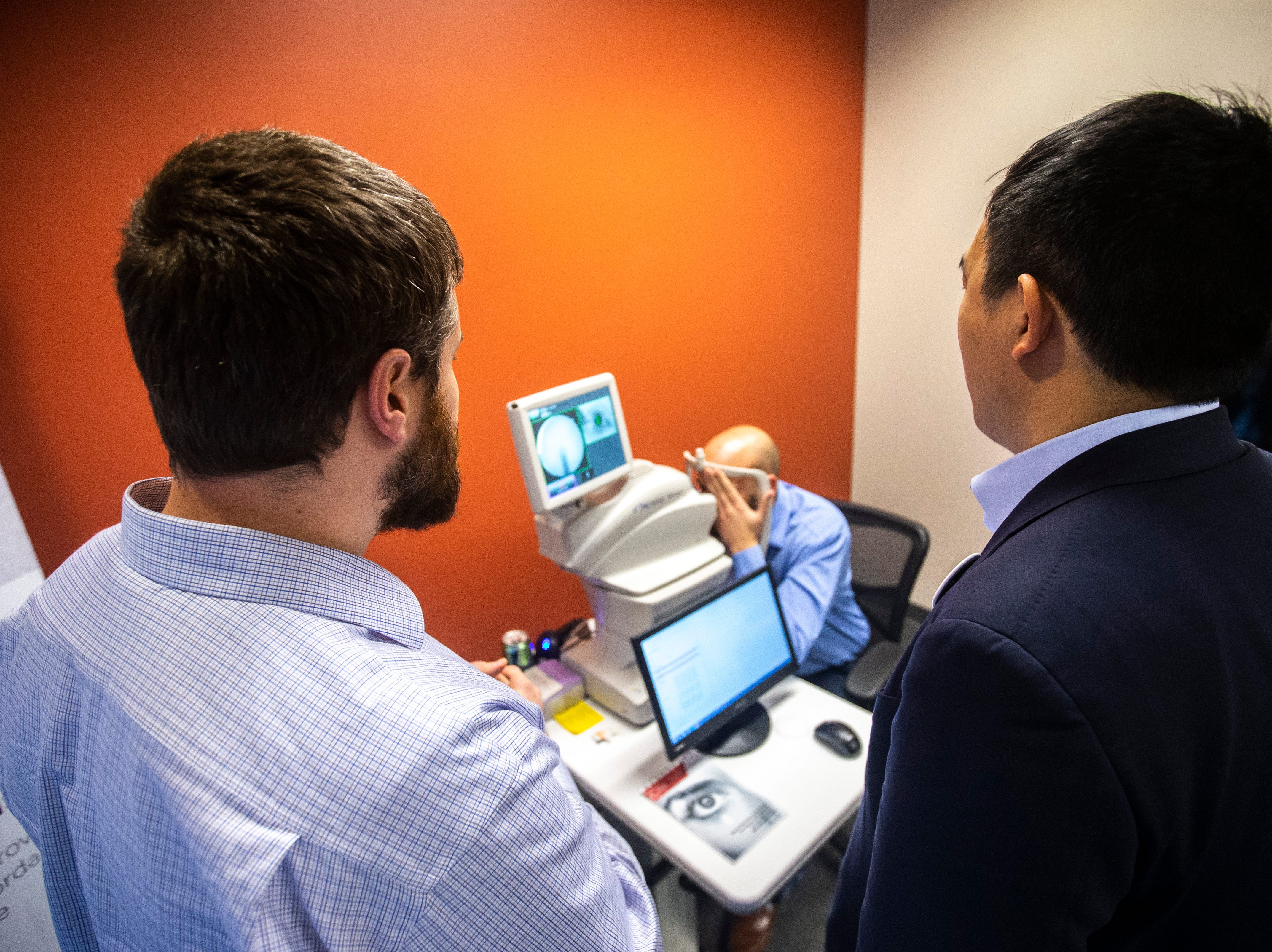 2020 presidential candidate Andrew Yang, right, is shown a demonstration of the IDx-DR, an AI diagnostic system that autonomously analyzes images of the retina for signs of diabetic retinopathy, on Wednesday, March 13, 2019, at IDx Technologies Inc. in Coralville, Iowa.