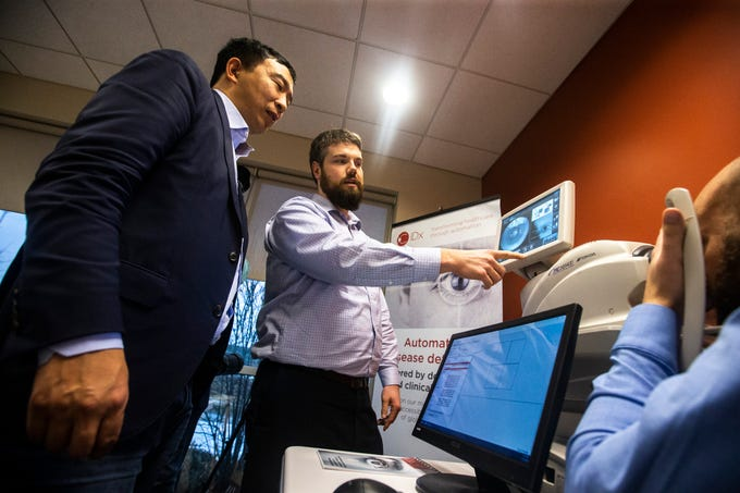 2020 presidential candidate Andrew Yang, left, is shown a demonstration of the IDx-DR, an AI diagnostic system that autonomously analyzes images of the retina for signs of diabetic retinopathy, on Wednesday, March 13, 2019, at IDx Technologies Inc. in Coralville, Iowa.