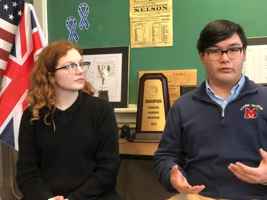 Sitting in front of one of the team's trophies, Robert Yin, a Madison senior on  the Academic Decathlon team, talks about the greatest moments of being a part of the team as Mary Hardy, also a senior, listens.