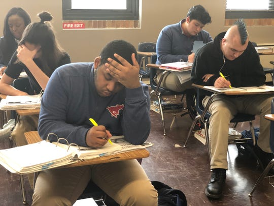 Academic Decathlon students highlight facts to study during their class time.