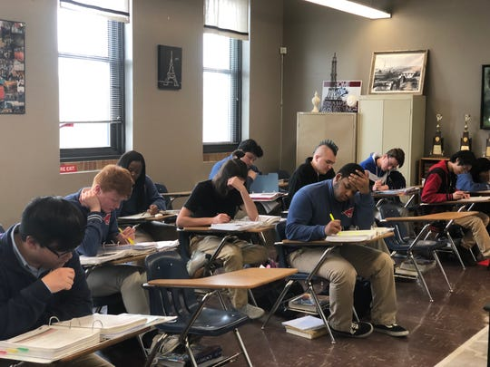 Surrounded by trophies, the Madison Academic High School Academic Decathlon team studies during their class time.