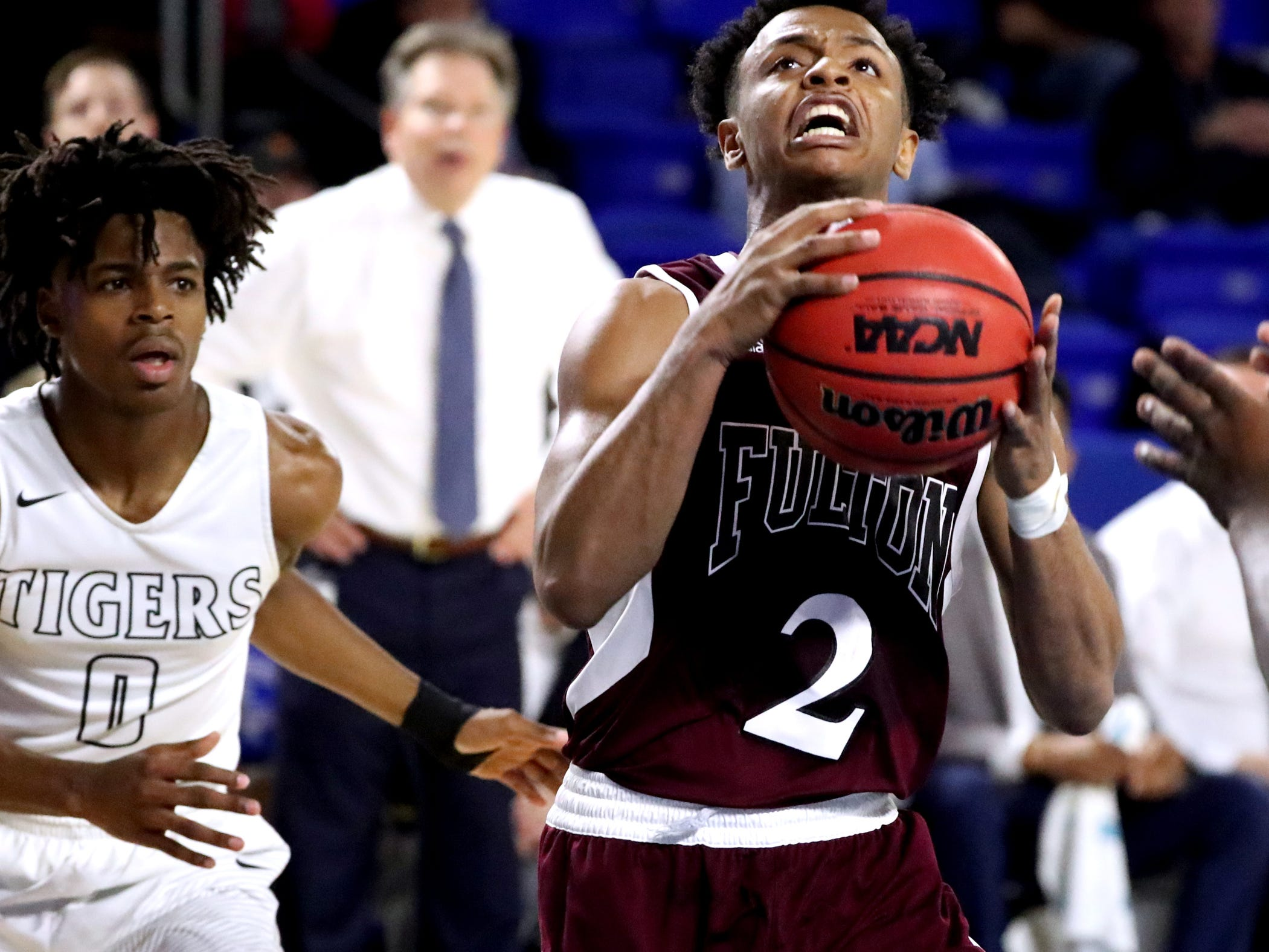 Fulton's Ron Davis III (2) ggoes up for a shot  as Mitchell's Michael Rice (0) moves in to guard him during the quarterfinal round of the TSSAA Class AA Boys State Tournament, on Wednesday, March 13, 2019, at Murphy Center in Murfreesboro, Tenn.