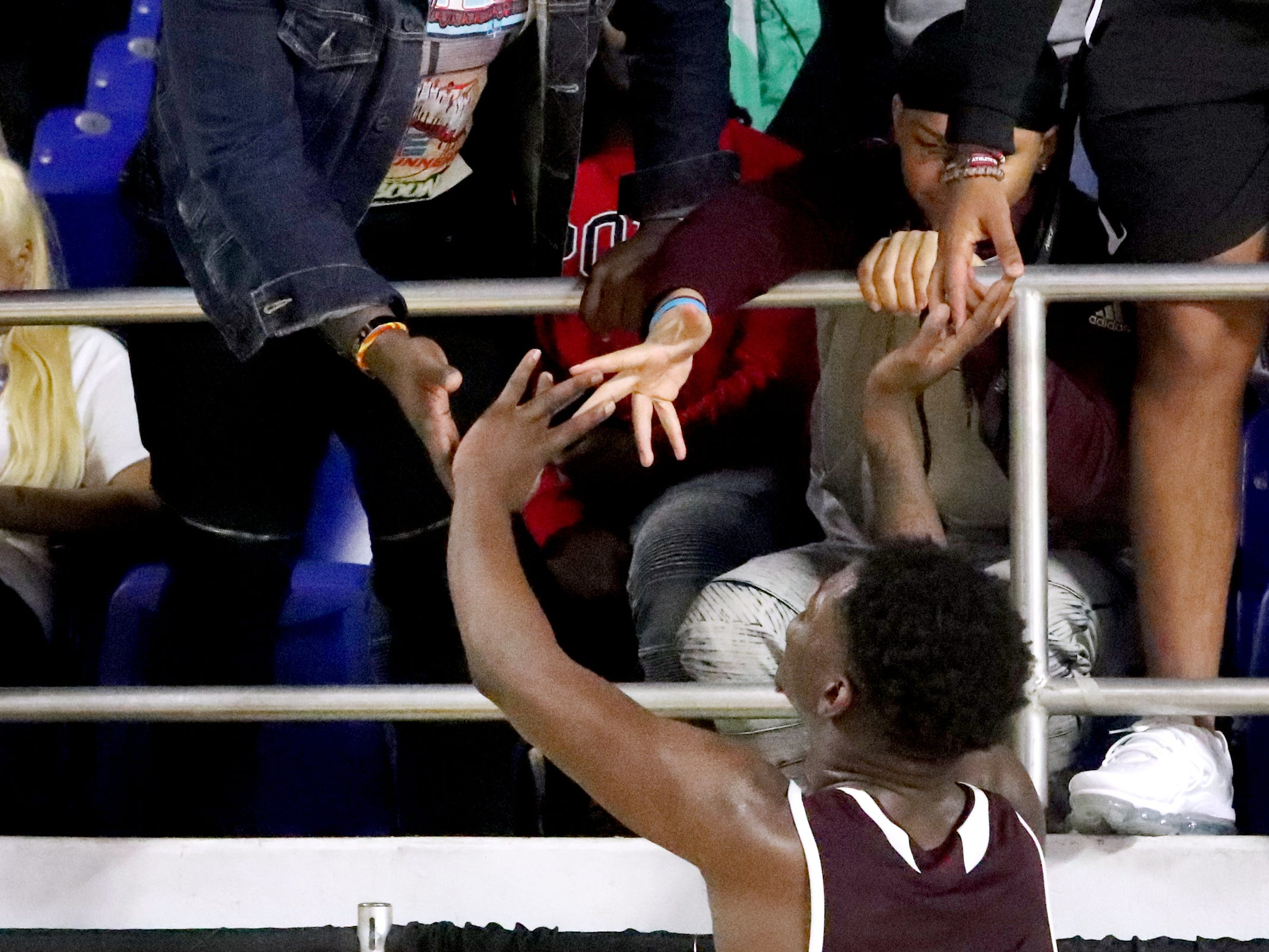 Fulton's Deshaun Page (32) celebrates the teams overtime win against Mitchell with the crowd after the quarterfinal round of the TSSAA Class AA Boys State Tournament, on Wednesday, March 13, 2019, at Murphy Center in Murfreesboro, Tenn.