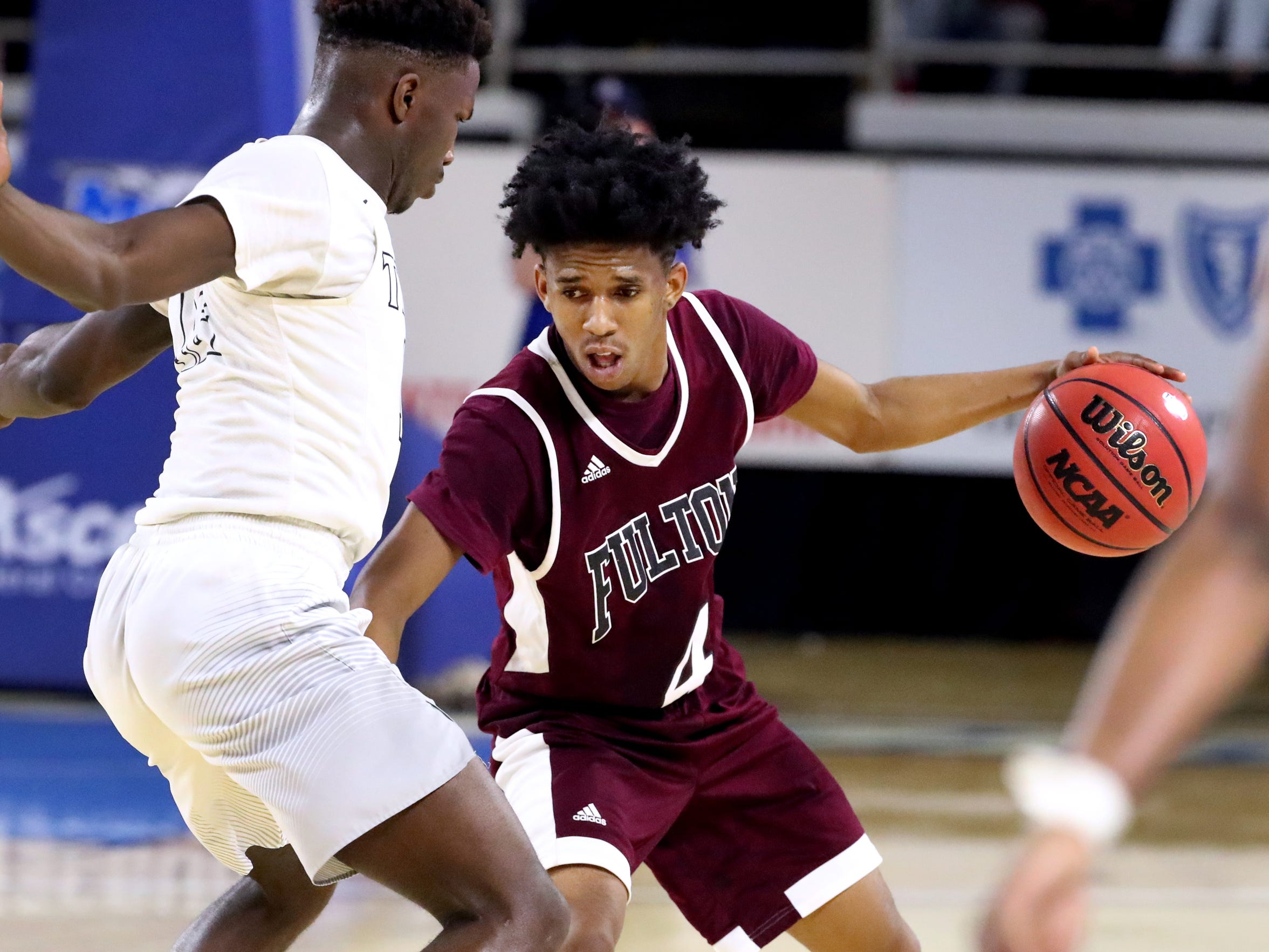 Fulton's Edward Lacy (4) brings the ball up court as Mitchell's Phabian Dale (12) guards him during the quarterfinal round of the TSSAA Class AA Boys State Tournament, on Wednesday, March 13, 2019, at Murphy Center in Murfreesboro, Tenn.