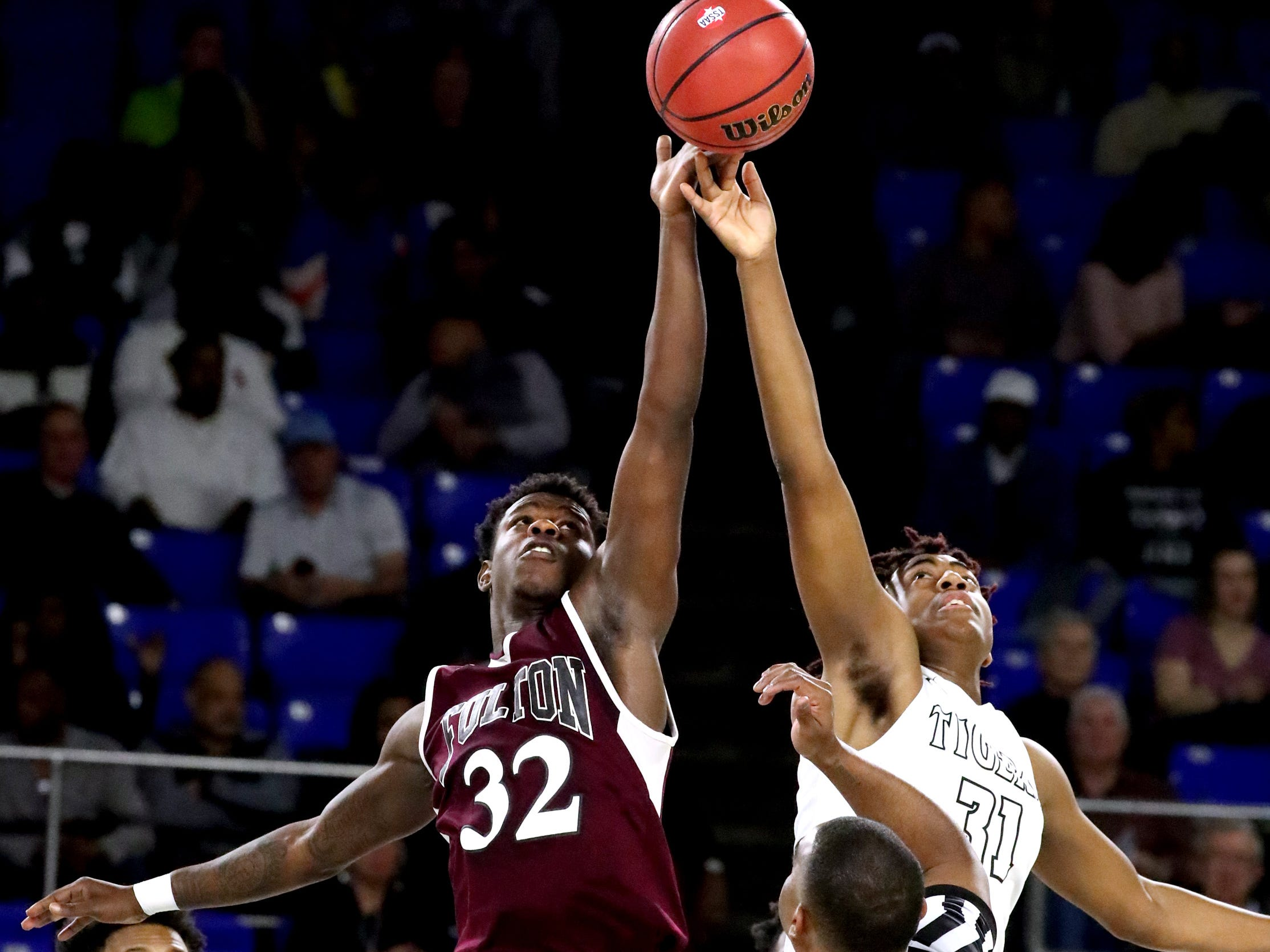 Fulton's Deshaun Page (32) and Mitchell's Justin Austin (31) jump the ball to start the game during the quarterfinal round of the TSSAA Class AA Boys State Tournament, on Wednesday, March 13, 2019, at Murphy Center in Murfreesboro, Tenn.