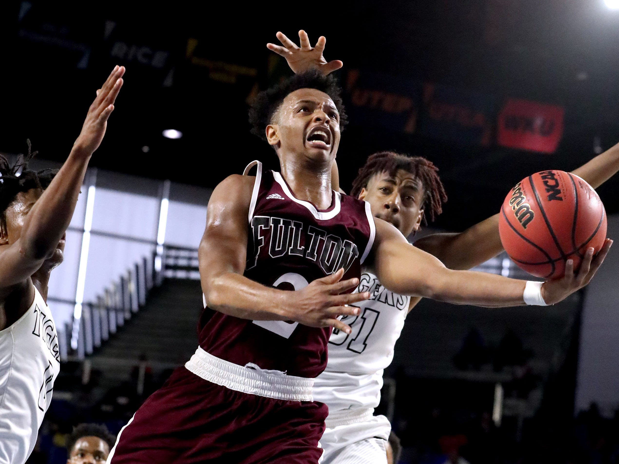 Fulton's Ron Davis III (2) shoots the ball between Mitchell's Michael Rice (0) and Mitchell's Justin Austin (31) during the quarterfinal round of the TSSAA Class AA Boys State Tournament, on Wednesday, March 13, 2019, at Murphy Center in Murfreesboro, Tenn.