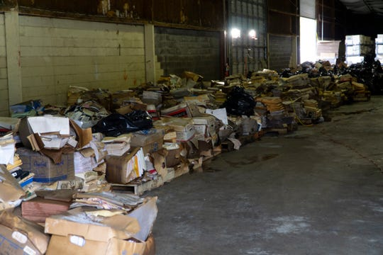 Debris and damaged materials line the walls of a warehouse in Knoxville that experienced several feet of flooding, resulting in major water damage.