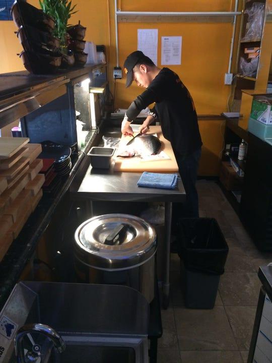 Cook Henry Zheng prepares a fish.