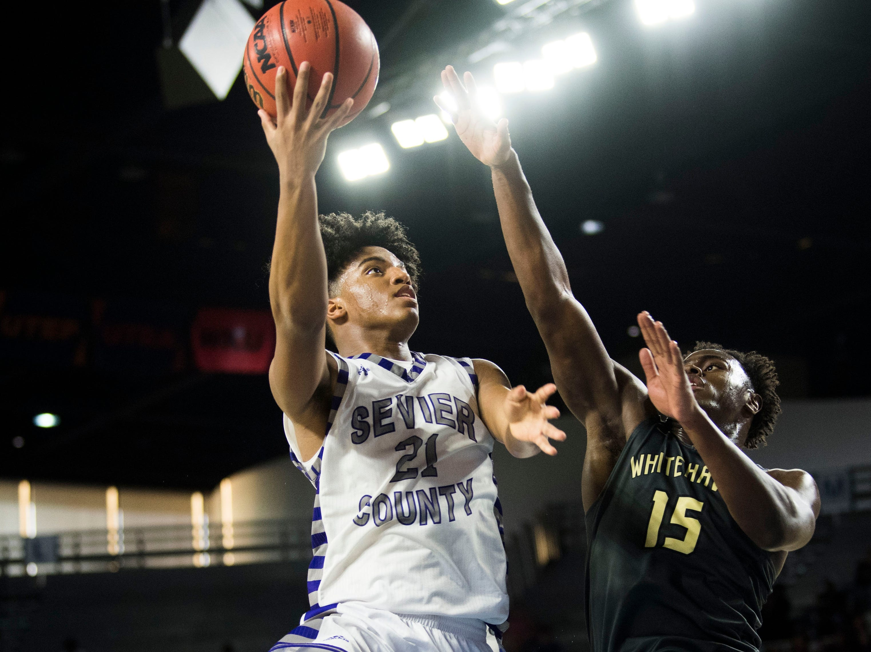 Sevier County's Cam Burden (21) takes a shot while defended by Whitehaven's Keveon Mullins (15) during a TSSAA AAA state quarterfinal game between Sevier County and Whitehaven at the Murphy Center in Murfreesboro, Wednesday, March 13, 2019.