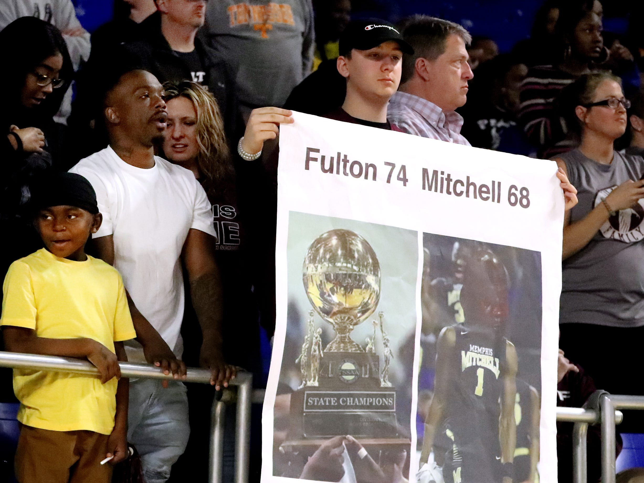A Fan hold up a banner in the crowd showing the results of a former matchup between Mitchell and Fulton in 2008 resulting in Fulton winning the State Championship, after Fulton beat Mitchell during the over time quarterfinal round of the TSSAA Class AA Boys State Tournament, on Wednesday, March 13, 2019, at Murphy Center in Murfreesboro, Tenn.