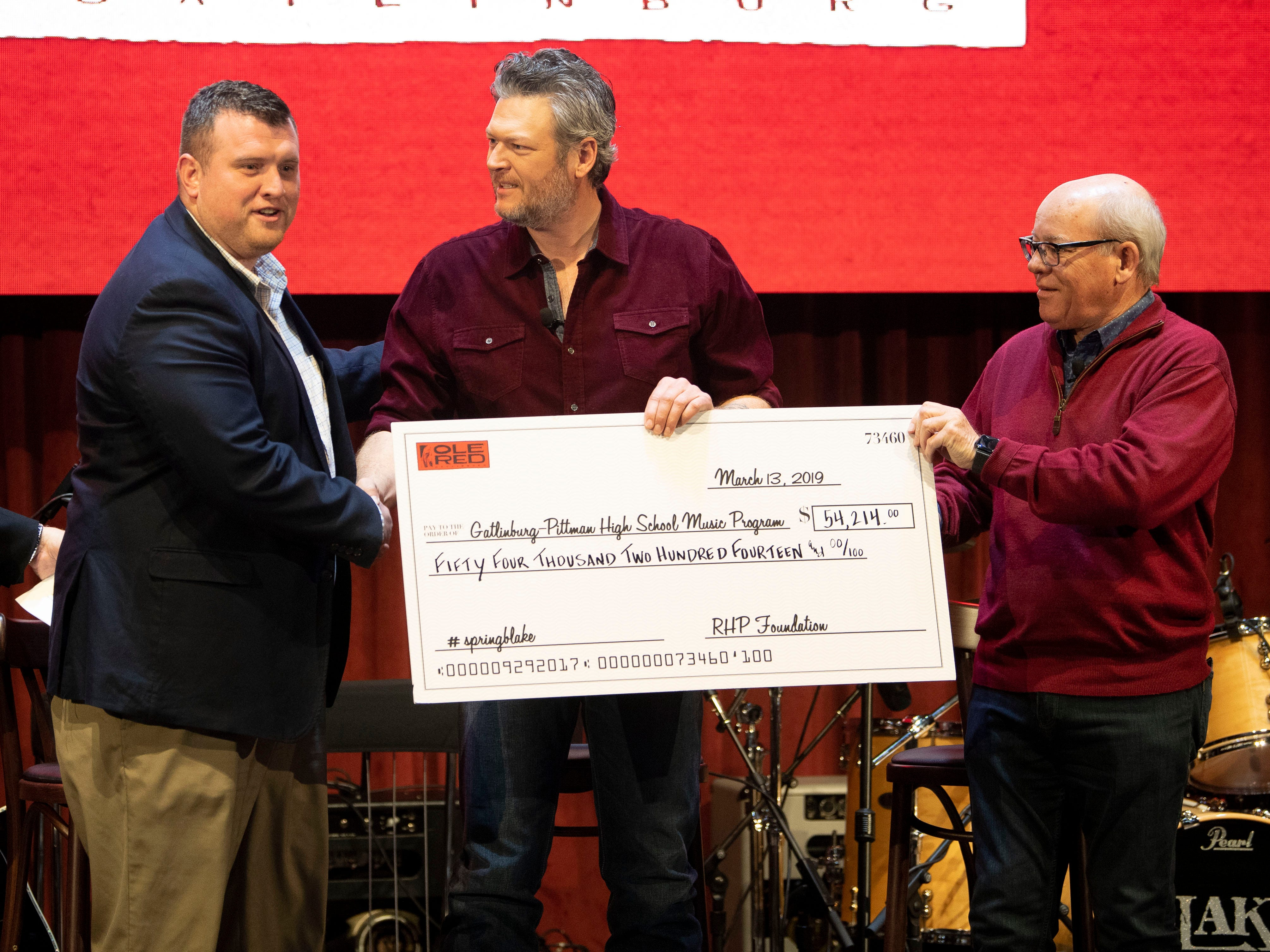 Gatlinburg-Pittman High School assistant principal AJ Bennett, left, accepts a check from Black Shelton and Ryman Hospitality Properties CEO Colin Reed for for $54,214 to benefit the music program at Gatlinburg-Pittman during a news conference for the grand opening of Ole Red Gatlinburg on Wednesday, March 13, 2019. The money was raised through auctioned tickets and donations for Shelton's grand opening concert at Ole Red Gatlinburg.