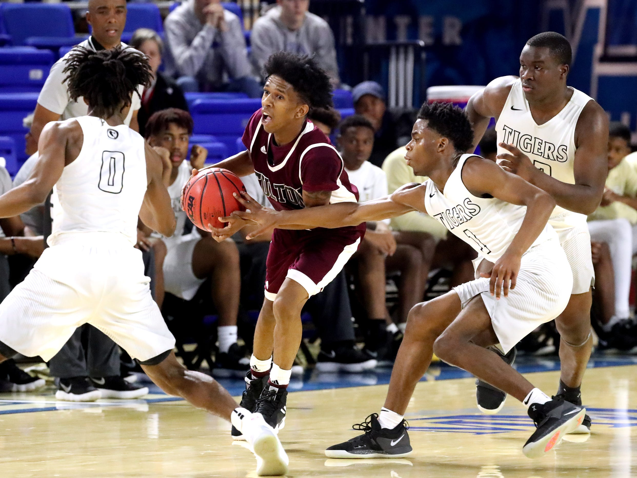 Fulton's Edward Lacy (4) brings the ball up court as he is guarded by Mitchell's Michael Rice (0), Mikell Rice (1) and Cameron Powers (32) during the quarterfinal round of the TSSAA Class AA Boys State Tournament, on Wednesday, March 13, 2019, at Murphy Center in Murfreesboro, Tenn.