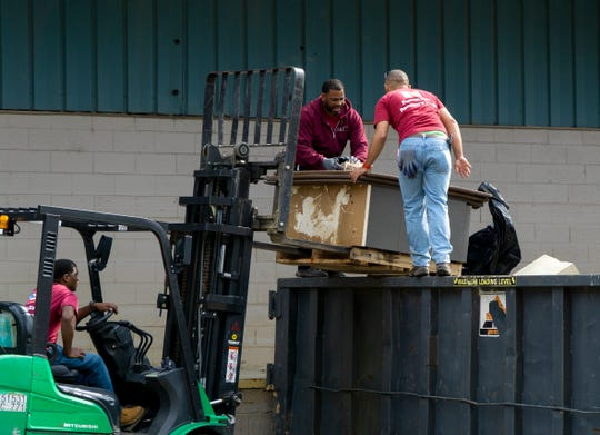 Workers load damaged furniture into a dumpster at warehouse on Prosser Road in East Knoxville following major flooding at the facility.