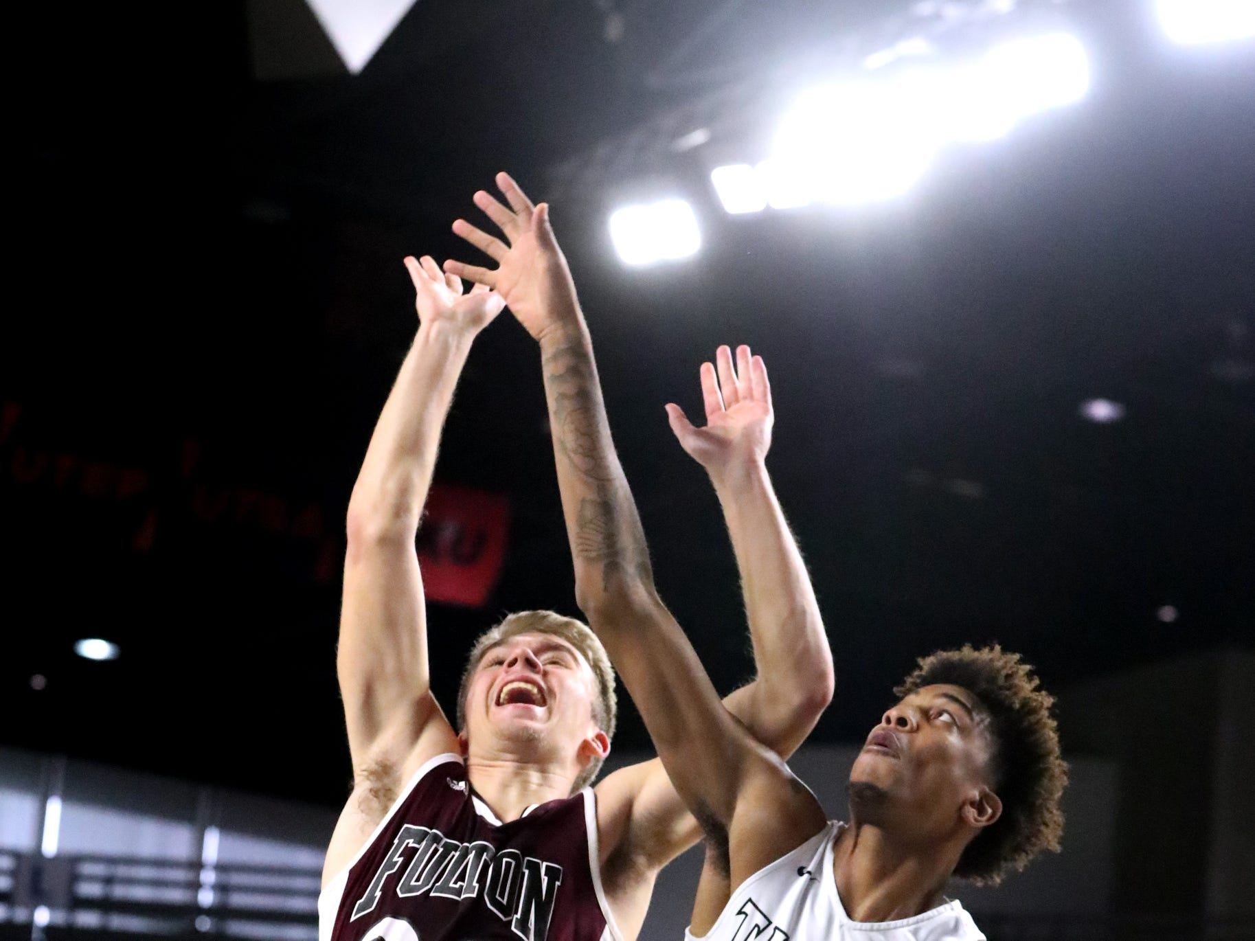 Fulton's Tommy Sweat (22) shoots the ball as Mitchell's Juwon Harris (3) and Mitchell's Cameron Powers (32) guard him during the quarterfinal round of the TSSAA Class AA Boys State Tournament, on Wednesday, March 13, 2019, at Murphy Center in Murfreesboro, Tenn.