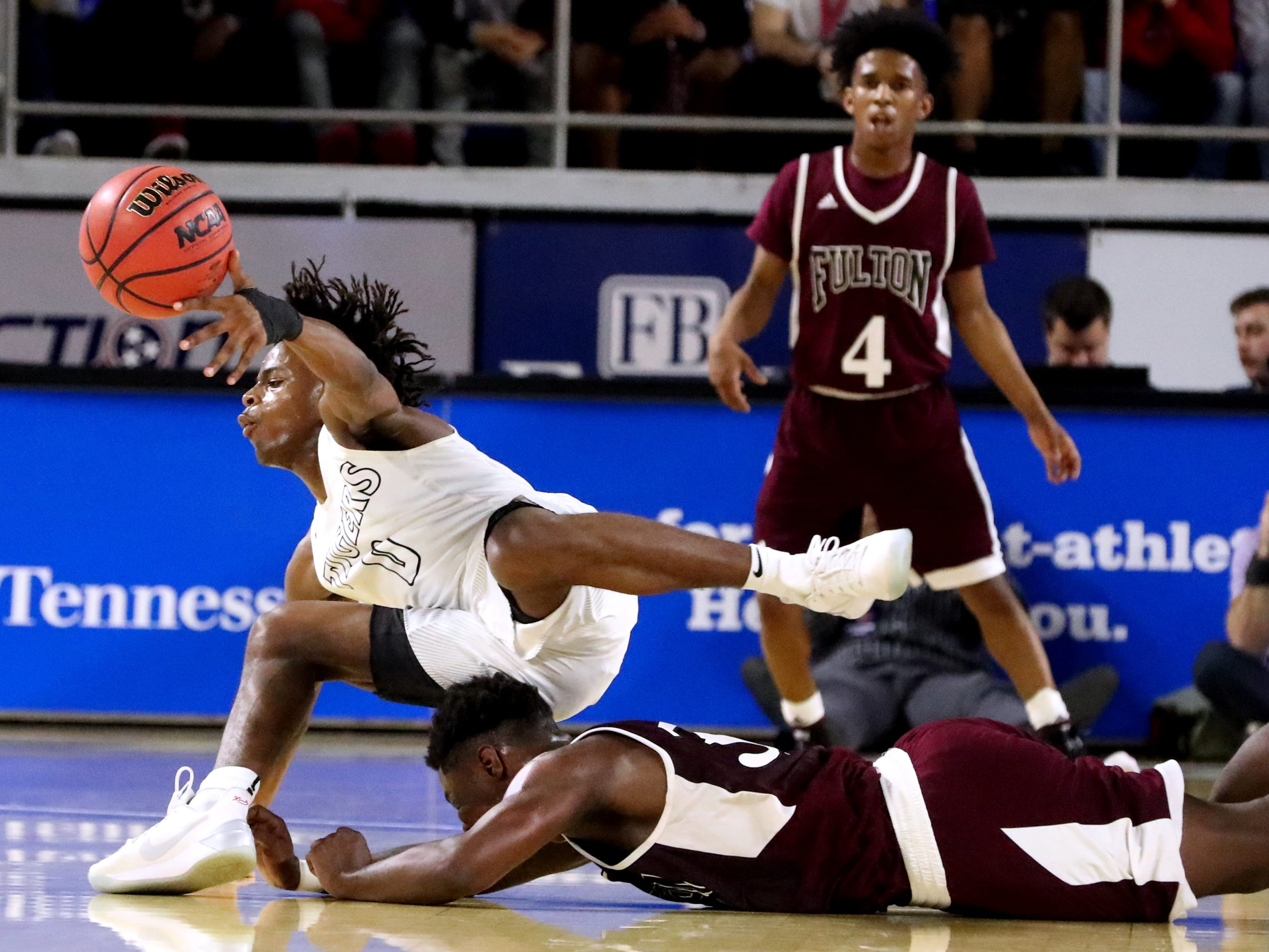 Mitchell's Michael Rice (0) trips over Fulton's Jashaun Fenderson (30) during the quarterfinal round of the TSSAA Class AA Boys State Tournament, on Wednesday, March 13, 2019, at Murphy Center in Murfreesboro, Tenn.