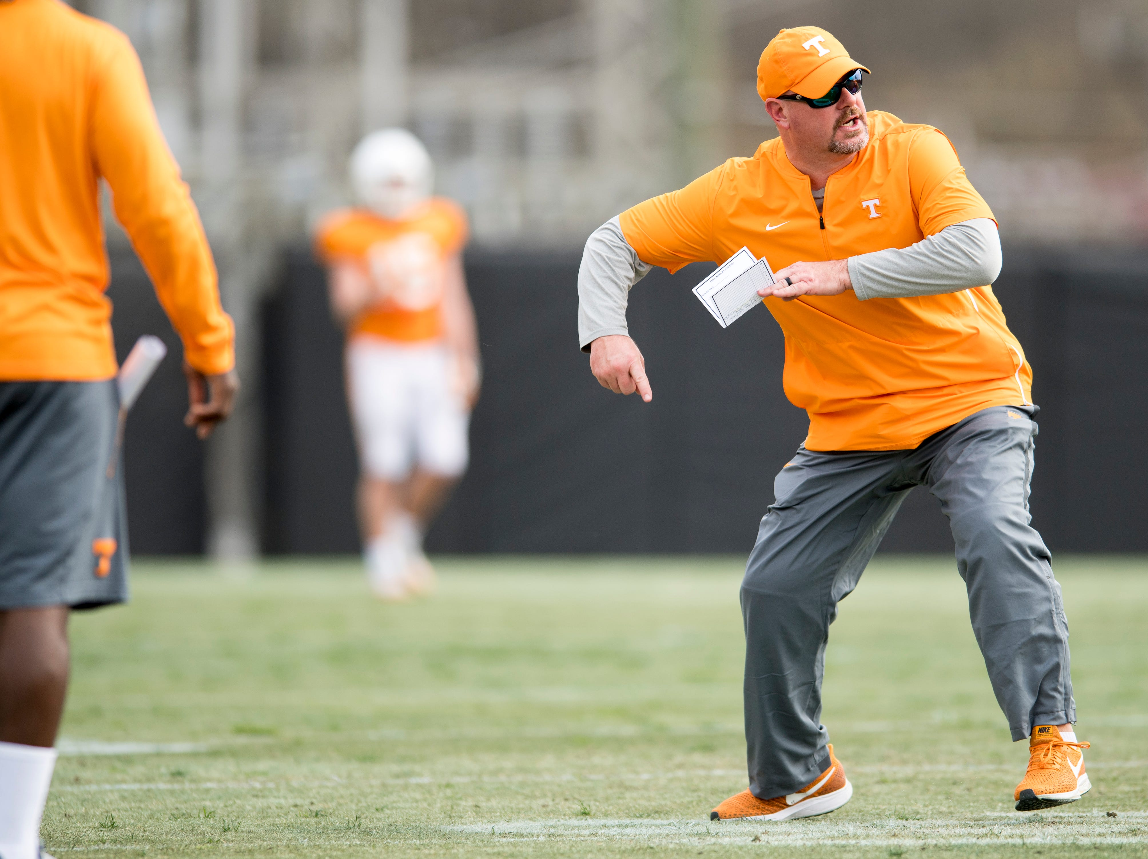 Tennessee offensive line coach Will Friend performs an example of a drill during Tennessee spring football practice at  Haslam Field in Knoxville, Tennessee on Wednesday, March 13, 2019.