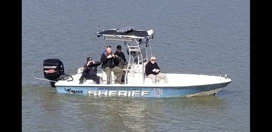 Investigators search the waters of Douglas Lake in Dandridge for evidence after human remains were found in a bag on the shore Sunday, March 10, 2019.