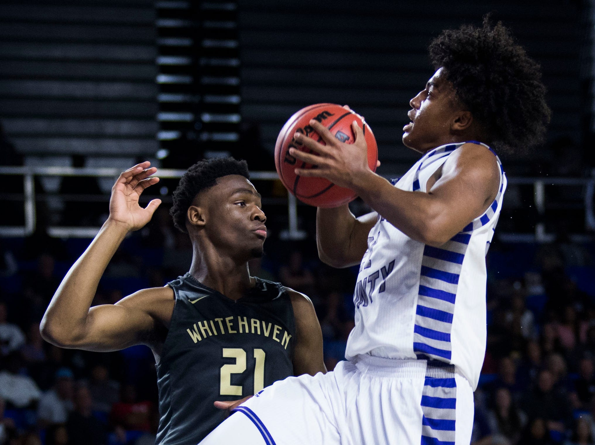 Sevier County's Cam Burden (21) takes a shot while defended by Whitehaven's Devine Owens (21) during a TSSAA AAA state quarterfinal game between Sevier County and Whitehaven at the Murphy Center in Murfreesboro, Wednesday, March 13, 2019.