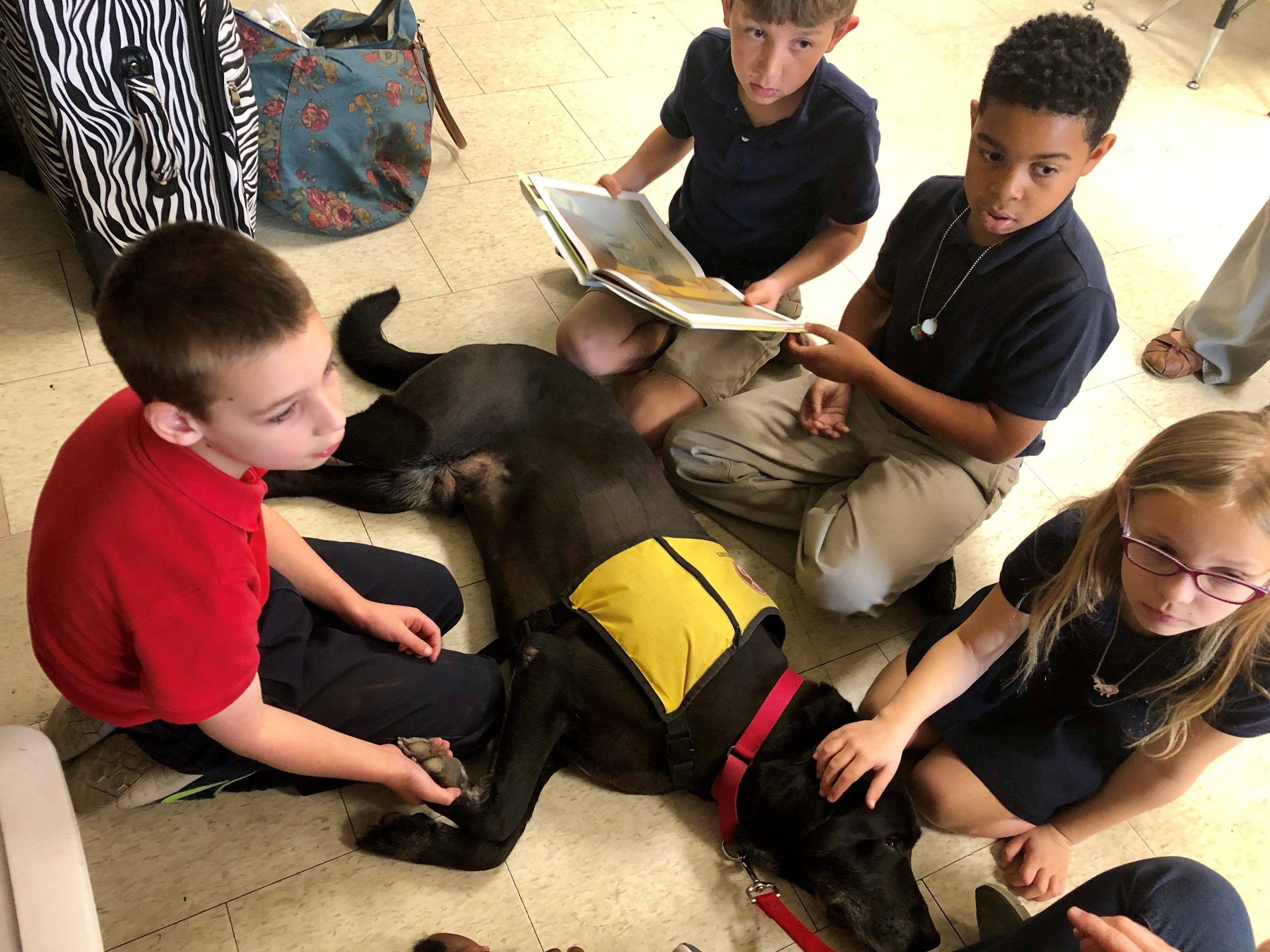 """Prairie Elementary second-graders read a book called """"Before You Were Mine"""" to therapy dog Chewy, a 7-year-old Labrador with Pet Partners, Wednesday."""