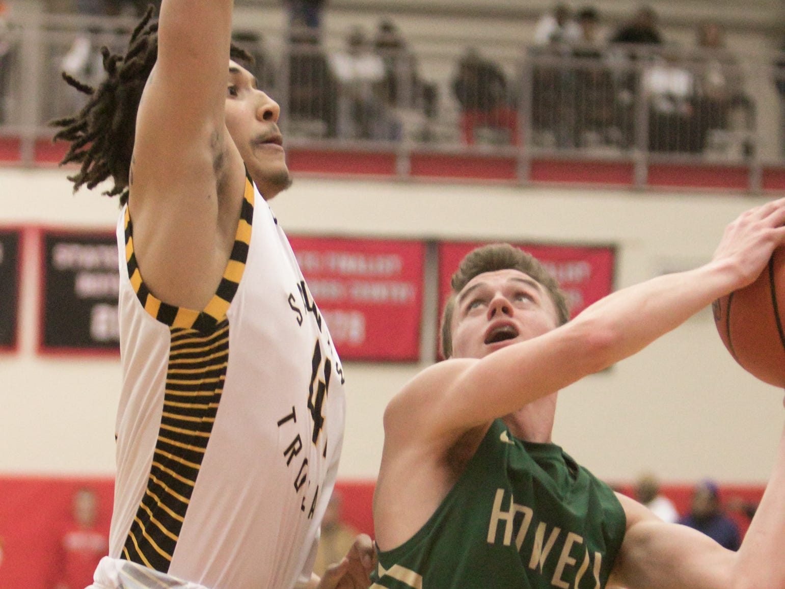 Howell's Kip French goes for a layup, guarded by Saginaw's Koby Barnett Tuesday, March 12, 2019.