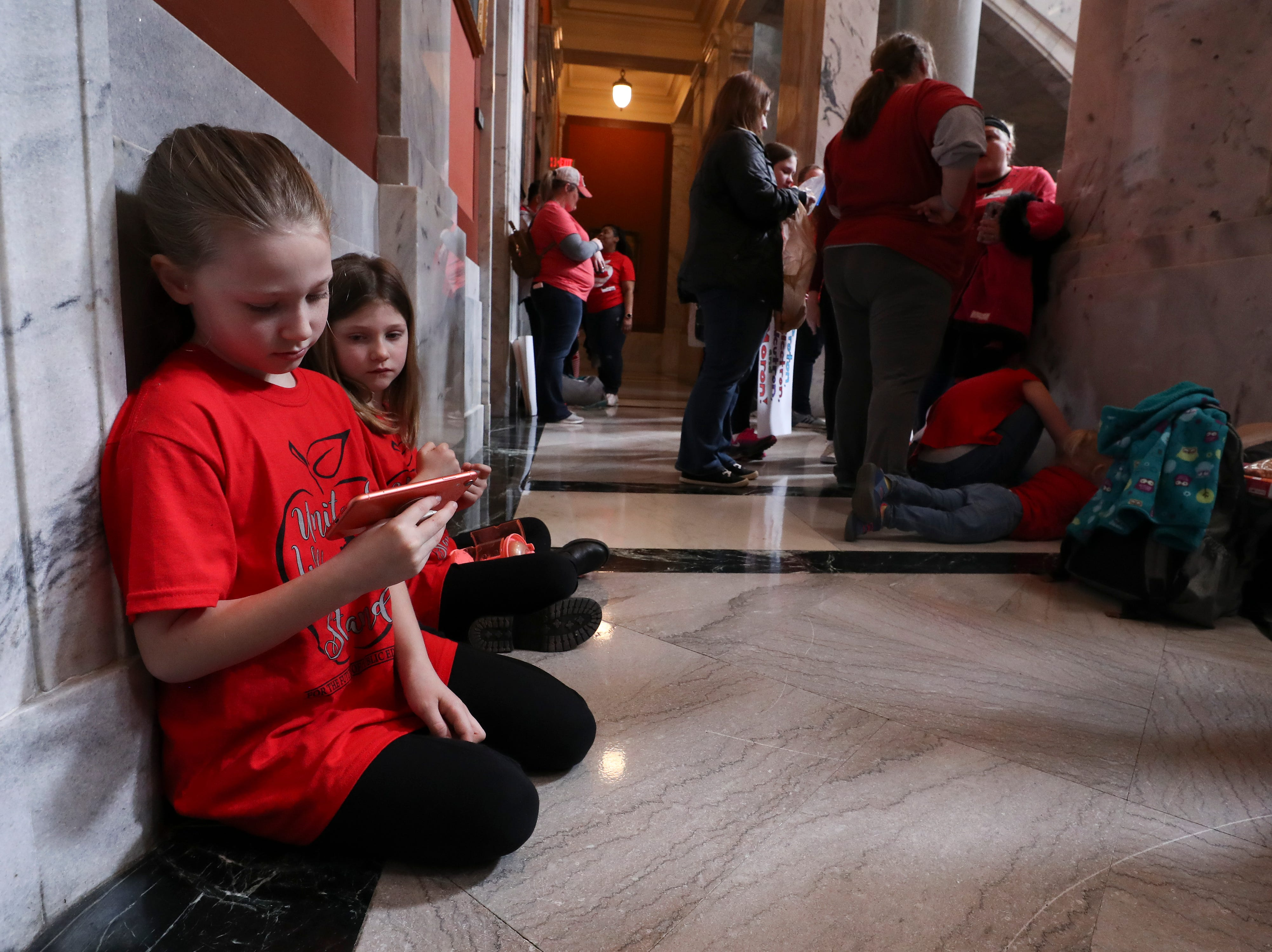 Reese McGohon, 8, left, and her sister Brynne McGohon, 6, watched a video on a cellphone as they attended the teacher protest with their mom, a Bullitt County social worker, in Frankfort. March 13, 2019