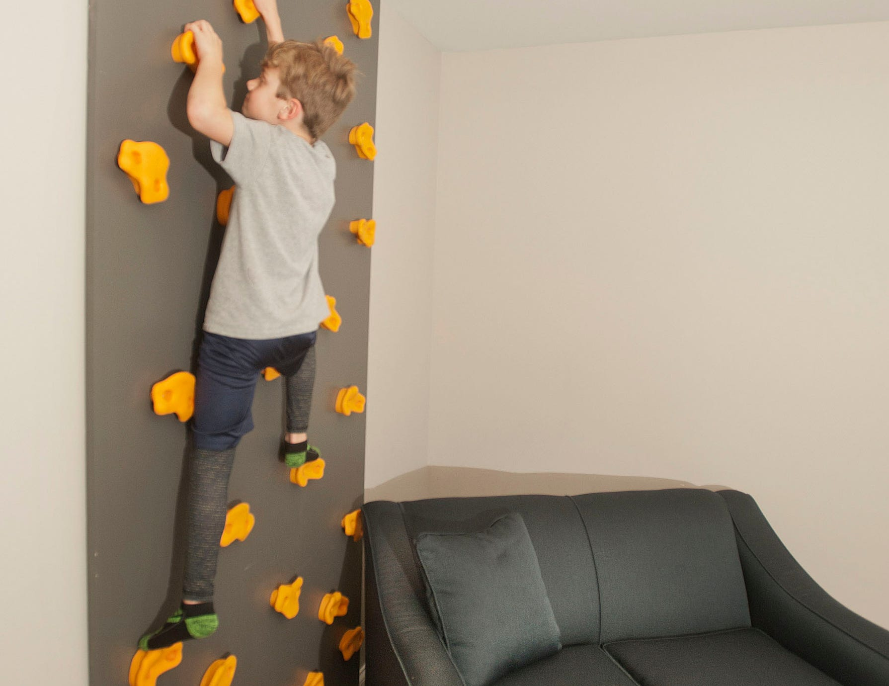 Ashur Hannah scales a climbing wall in the family's basement.01 March 2019