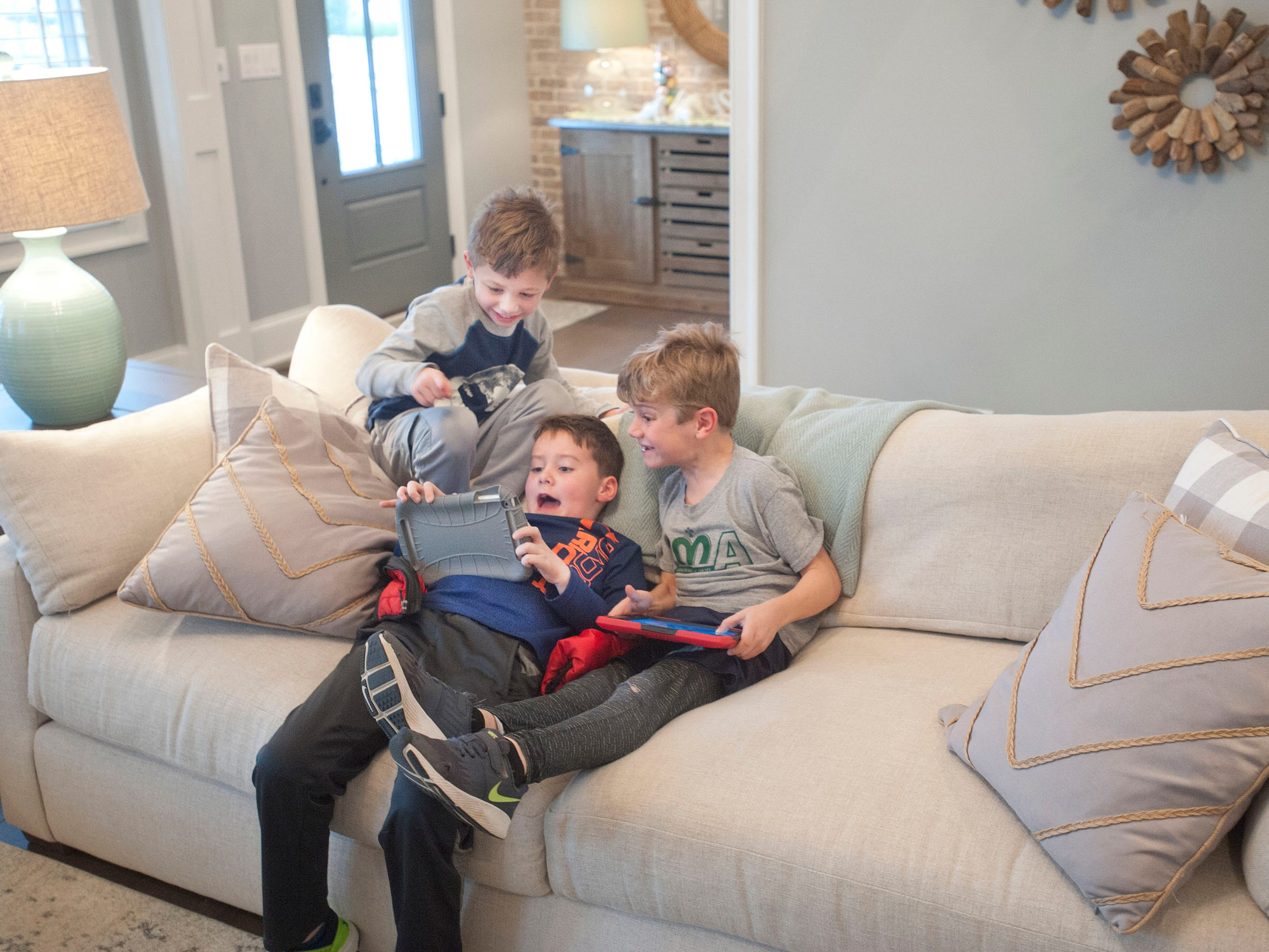 Ellis Hannah, age 5, top left, hi brother Ashur, age 7, right, and next door neighbor Will Droppleman, age 6, play computer games together in the Hannah living room.01 March 2019