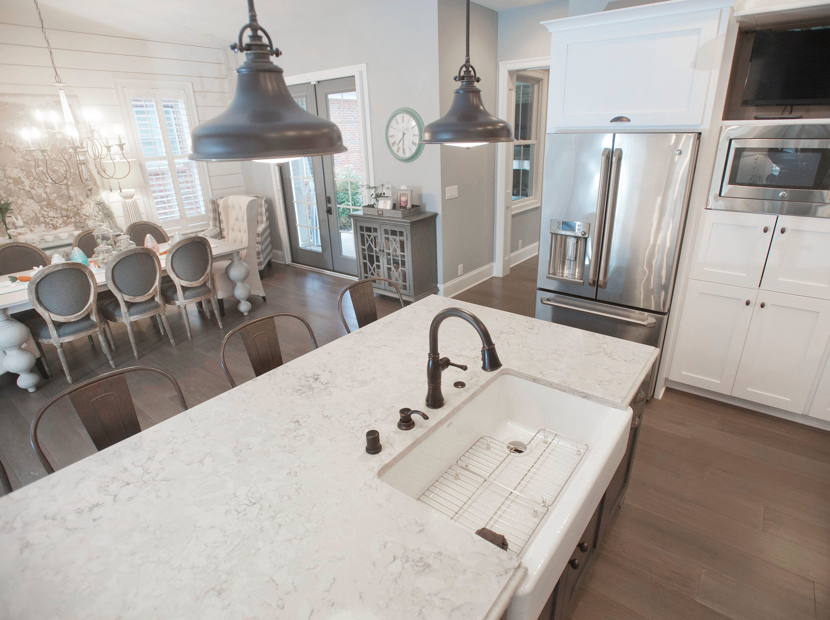 The kitchen of the Hannah home features a farm sink in the kitchen island. The open concept includes the dining room, top left.01 March 2019