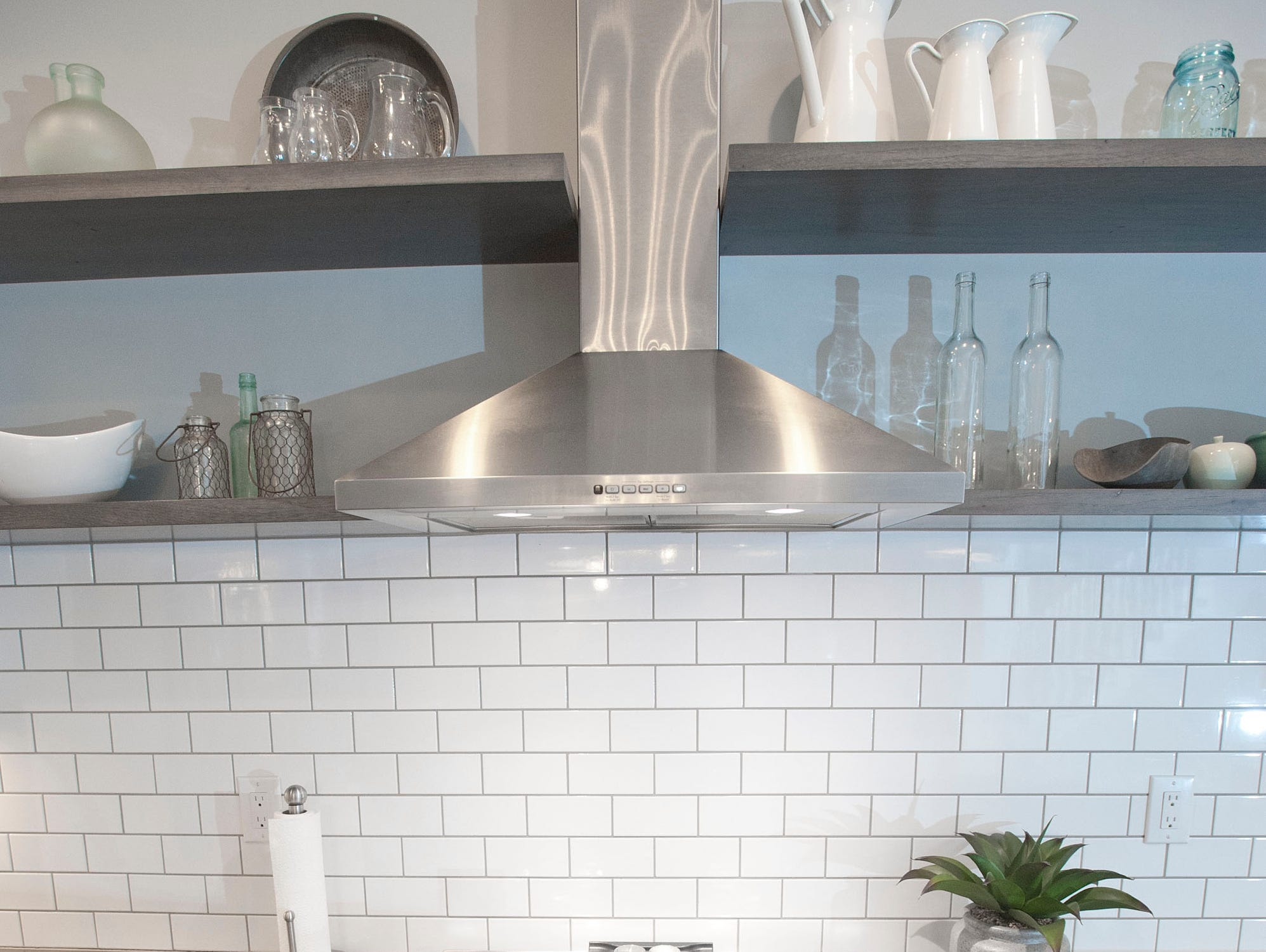 The Hannah kitchen includes a farm sink and floating shelves between the cabinets. The backsplash is subway tile.01 March 2019