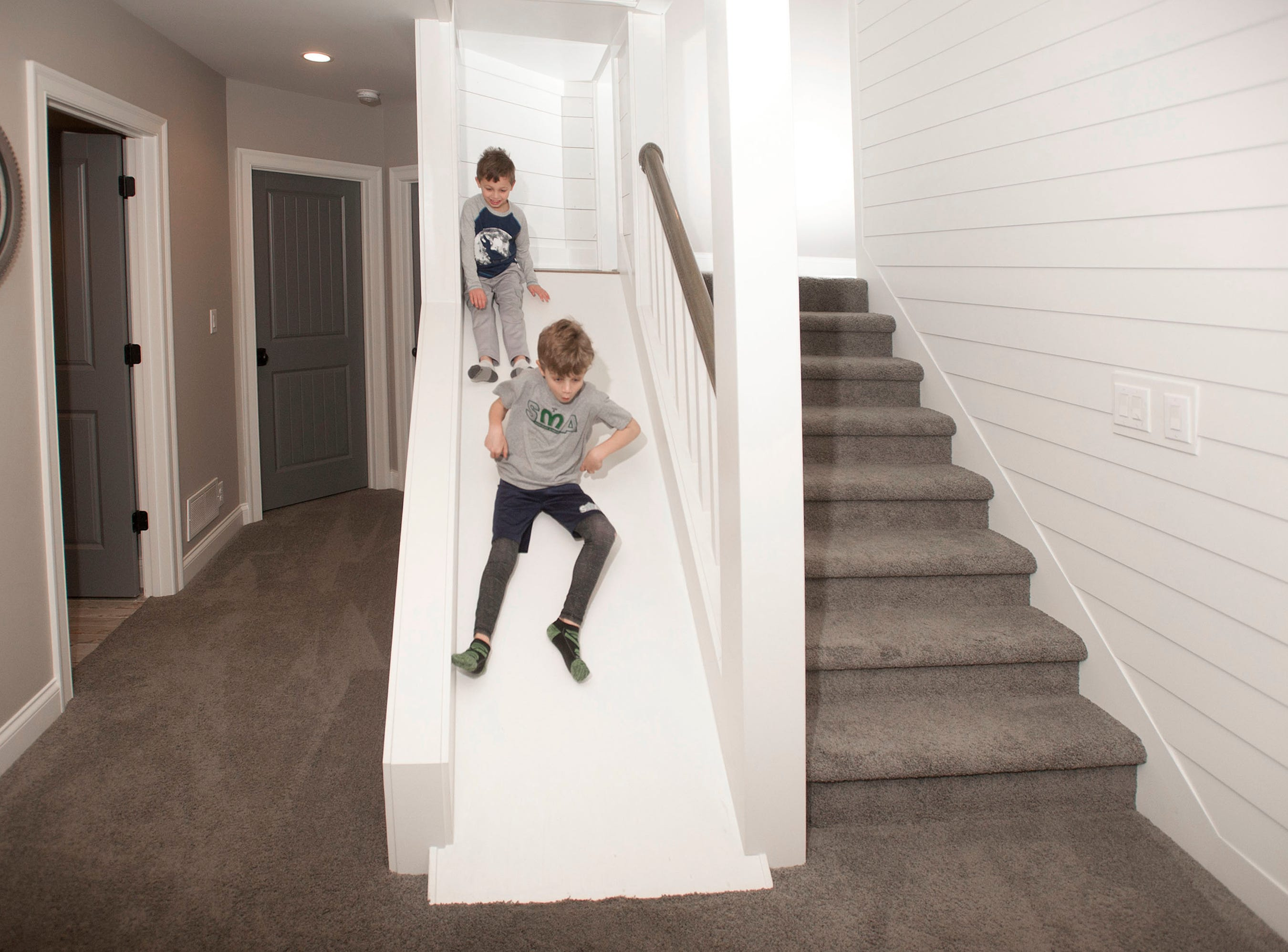 Ellis (top) and Ashur (bottom) Hannah head down a slide built alongside the stairwell to the basement family room.01 March 2019