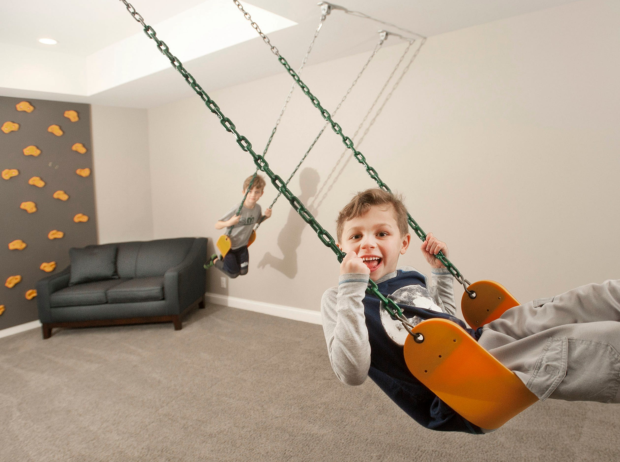 Ellis (right) and Ashur (left) Hannah play on a swing set hanging in the home's basement. At far left is a climbing wall for the boys, ages 5 and 7.01 March 2019