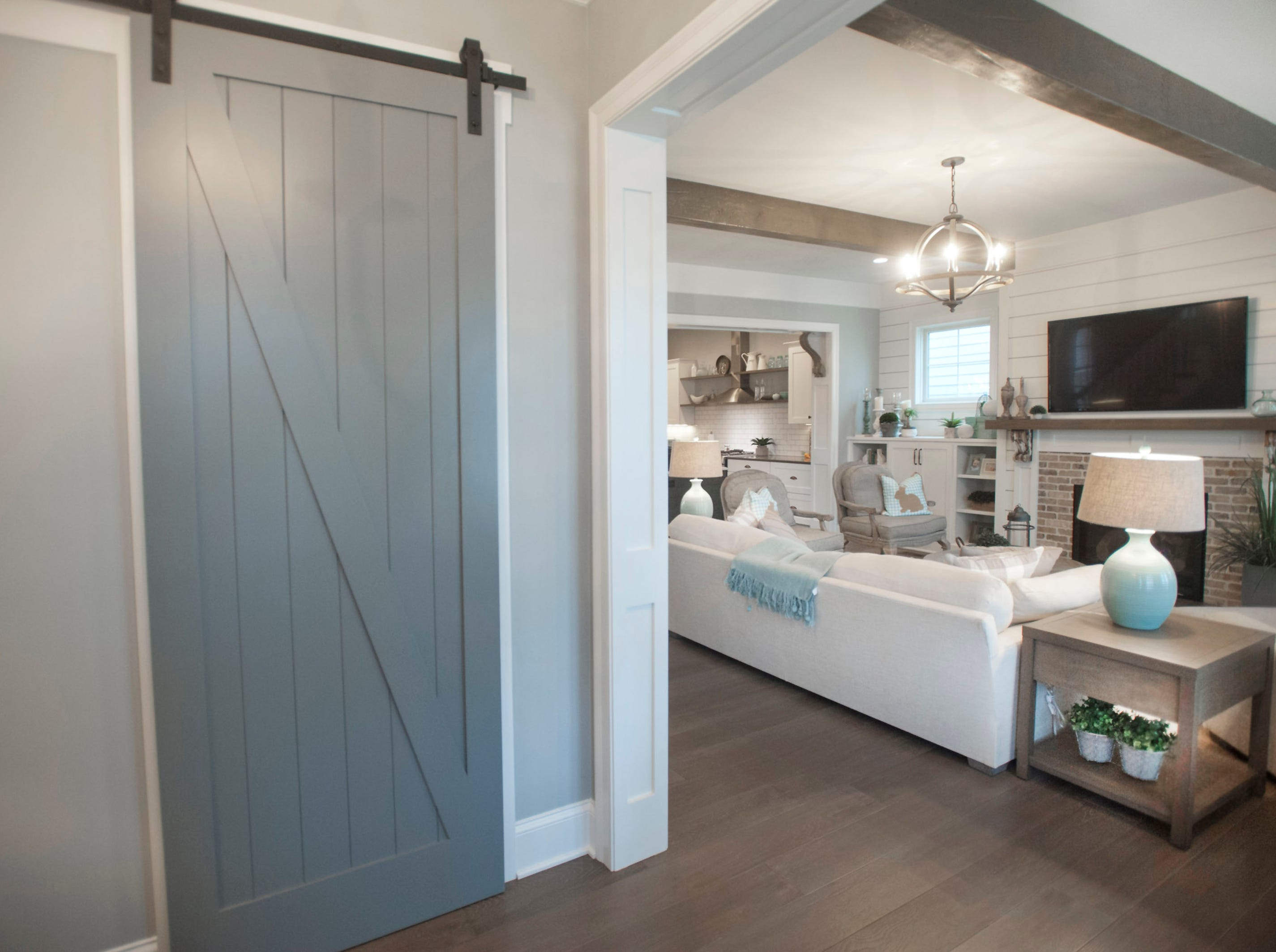 The entrance foyer of the Hannah home in Norton Commons features a coat closet with a barn door. The living room is at right.01 March 2019