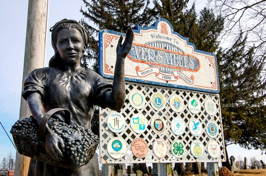 A statue of a woman holding her harvest of grapes waves to welcome you into the Village of Versailles on Tuesday, March 12, 2019, in Versailles, Ohio.