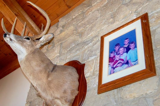 A 10-point buck is mounted next to a family photo in the Ahrens' living room on Tuesday, March 12, 2019, in Versailles, Ohio.