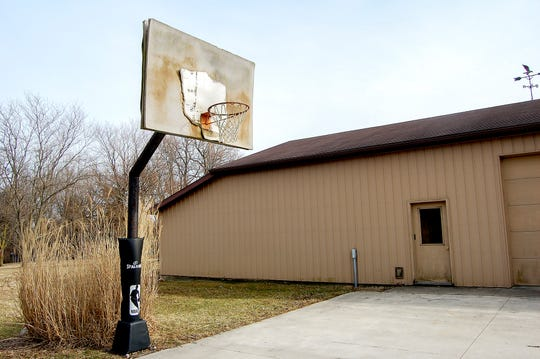 The old basketball hoop with a beat-up backboard still sits in the Ahrens family's driveway on Tuesday, March 12, 2019, in Versailles, Ohio.