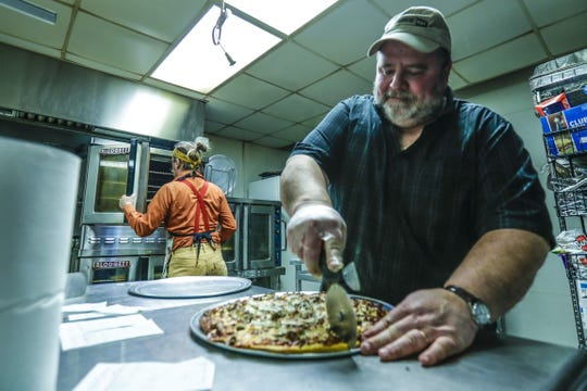 Dale Frank slices a pizza for customers at Marilyn's Fire Station & Catering in Medford.