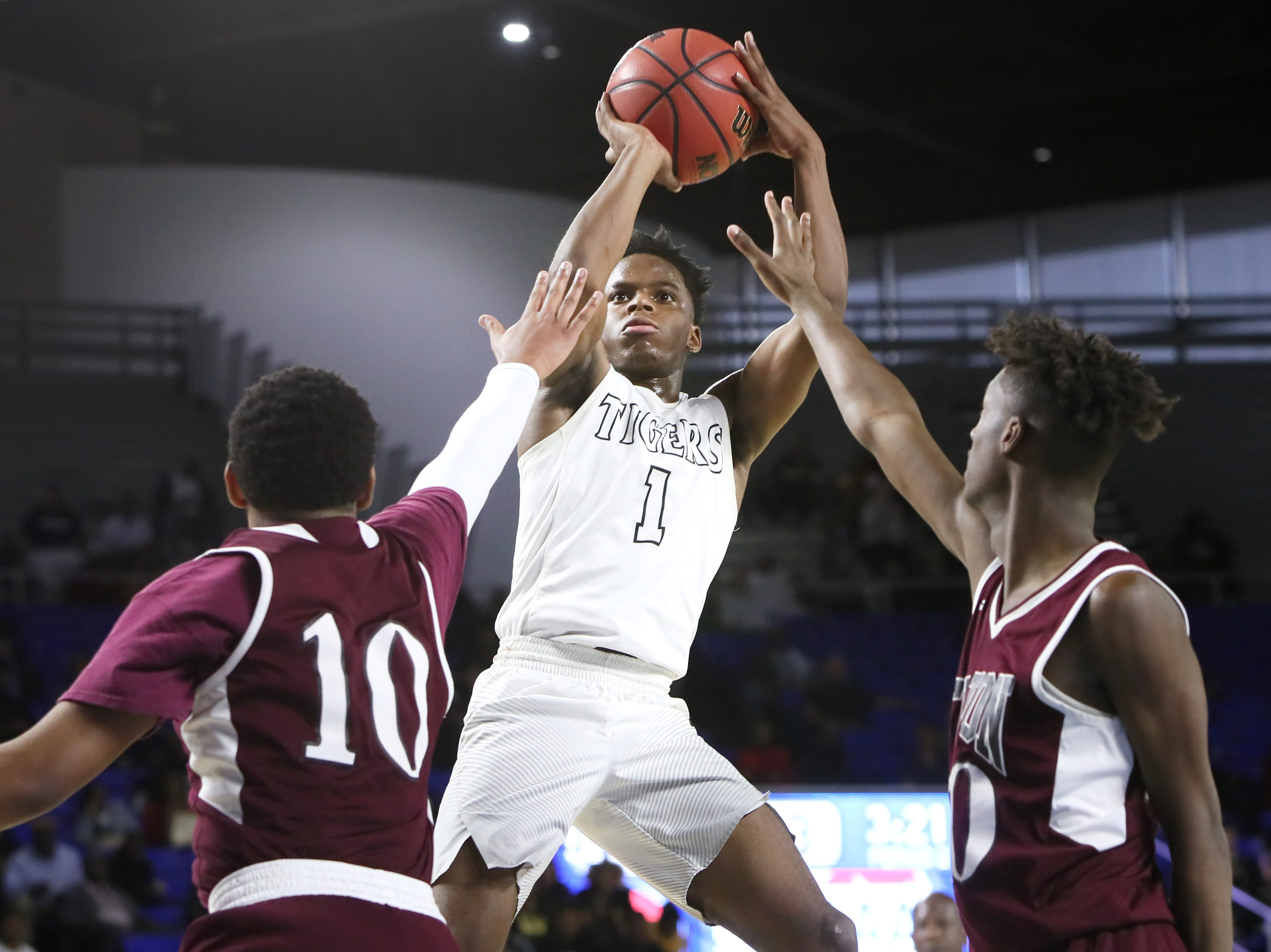 Mitchell's Mikell Rice shoots the ball over Fulton's Trey West, left, and Domenic Holland during the TSSAA Division I basketball state tournament in Murfreesboro on Wednesday, March 13, 2019.