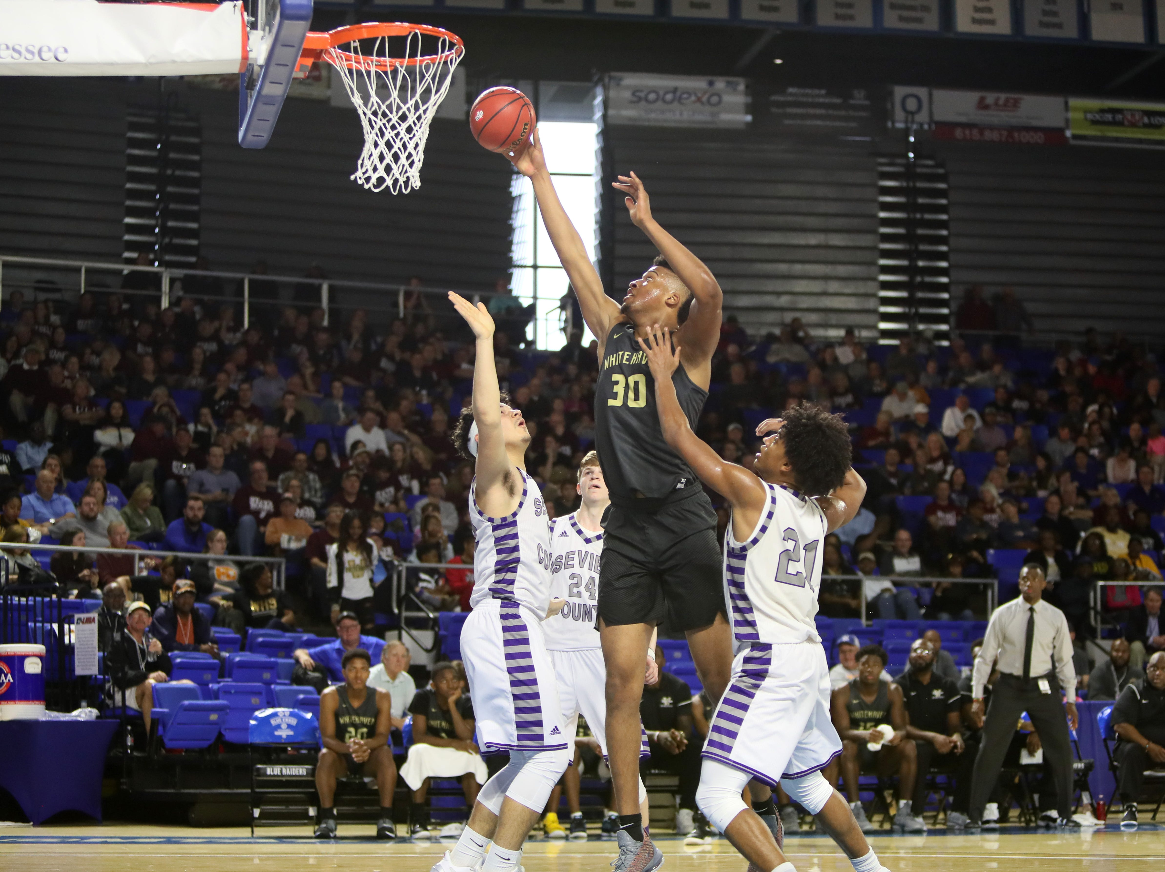 Whitehaven's Jordan Wilmore shoots the ball over Sevier County's Tyler Wilson, left, and Cam Burden during the TSSAA Division I basketball state tournament at the Murphy Center in Murfreesboro, Tenn. on Wednesday, March 13, 2019.