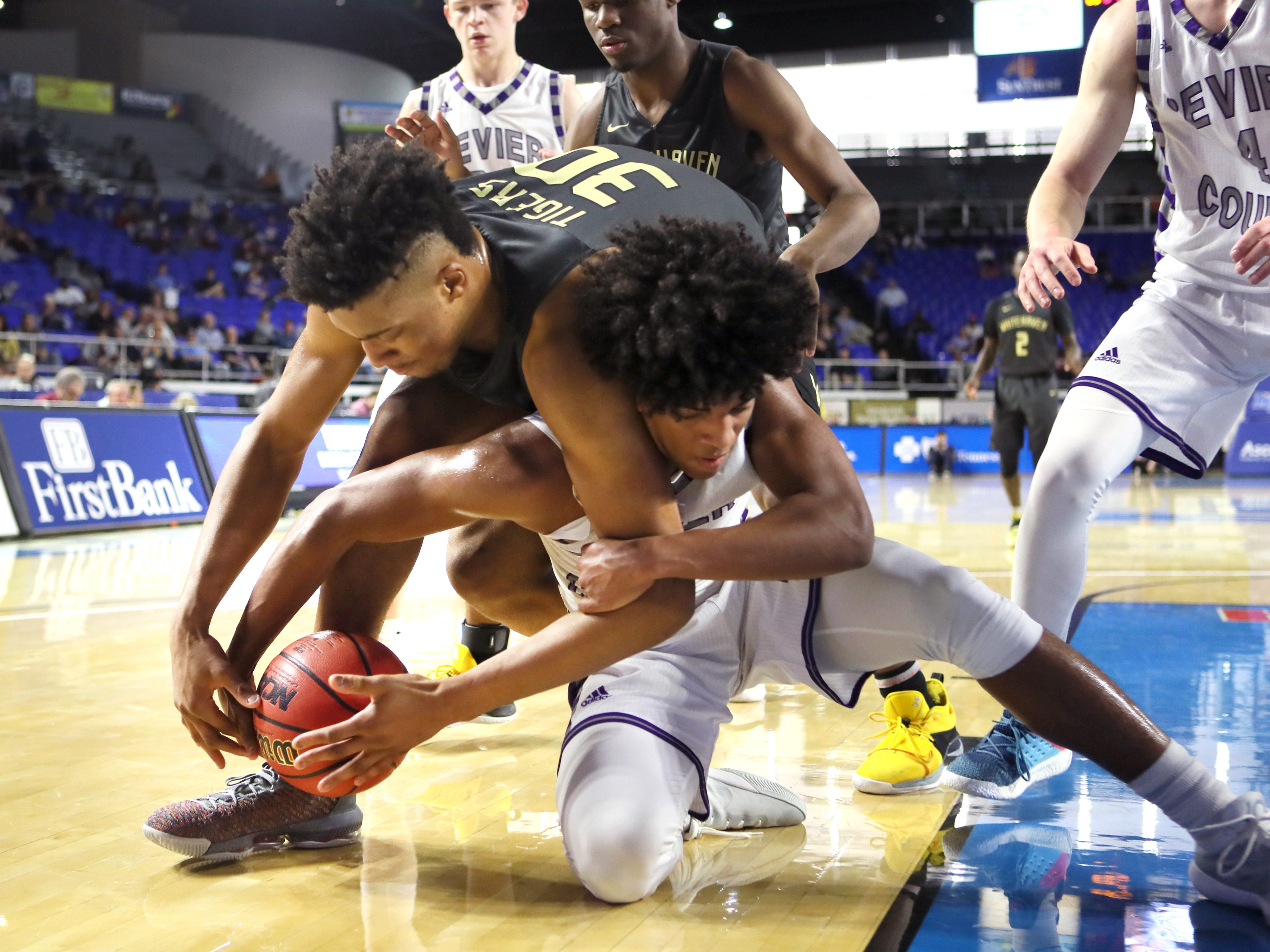 Whitehaven's Jordan Wilmore fights for a loose ball with Sevier County's Cam Burden during the TSSAA Division I basketball state tournament at the Murphy Center in Murfreesboro, Tenn. on Wednesday, March 13, 2019.