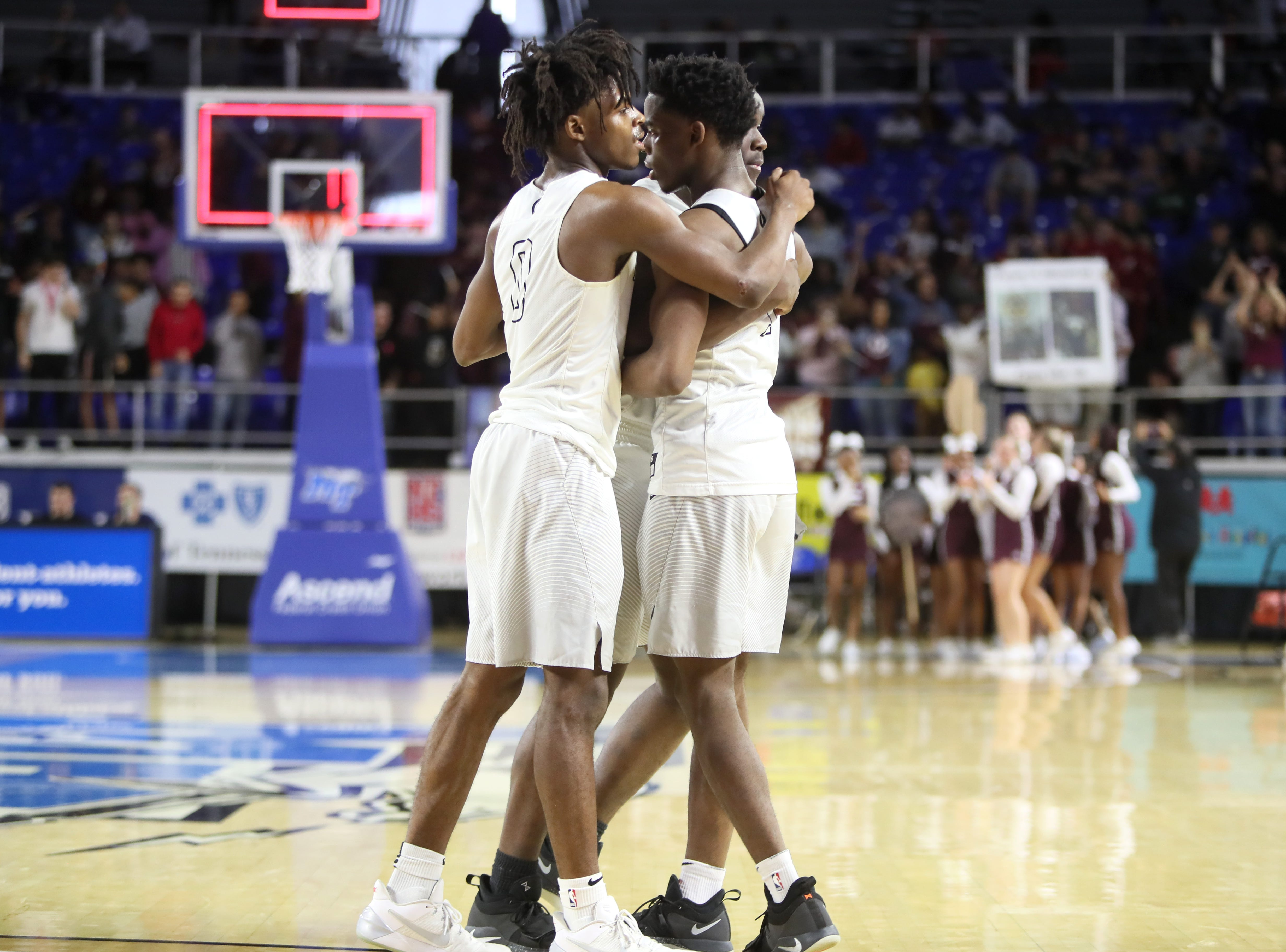 Mitchell Brothers Michael Rice and Mikell Rice embrace teammate Cameron Powers after their 44-41 overtime loss to Fulton during the TSSAA Division I basketball state tournament in Murfreesboro on Wednesday, March 13, 2019.