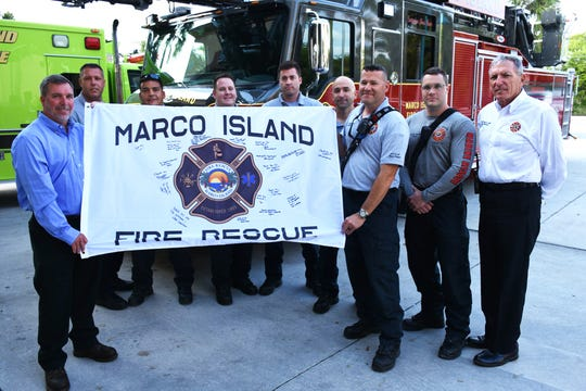 Surrounded by Marco Island firefighters including Chief Mike Murphy, right, Scott Greenwell, left, father of the command pilot, and MIFD Capt. Leo Rodriguez hold the departmental flag that flew along on the Army missions. The Marco Island Fire-Rescue Dept. had a departmental flag flown on combat medevac missions on an Army helicopter in Syria, and signed by all the crew, including the command pilot, who has a personal connection.